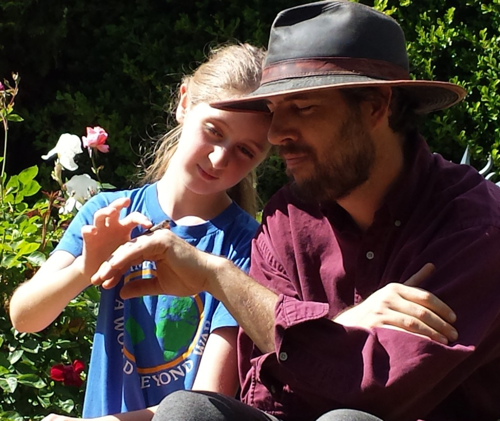 Charles Peden and daughter Maya petting baby lizard