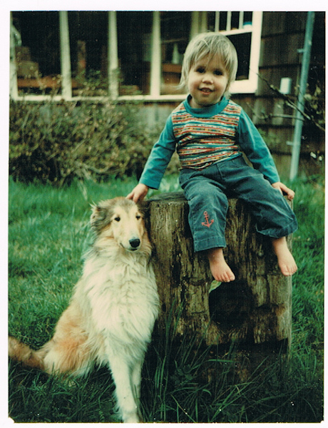 Charles Peden as a young boy of about two years old sitting on a tree stump with the family dog, a sheltie (similar to a collie) sitting beside him on the green grass. In the background of this photograph from 1976 you can see the front of an old house.