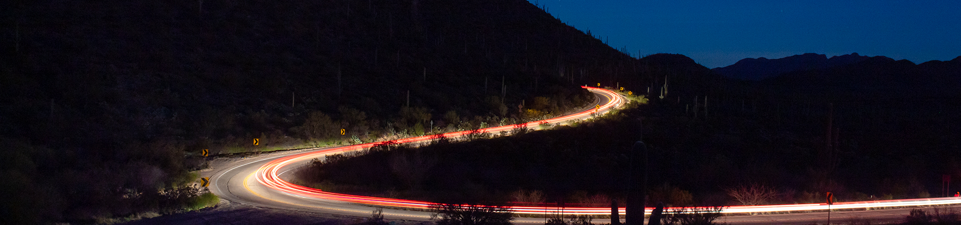 Light trails of passing vehicles on Picture Rocks road in Saguaro National Park West, outside of Tucson, Arizona in the Sonoran Desert.